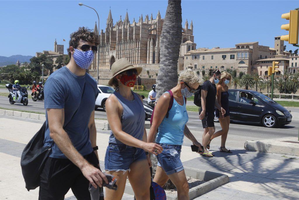 Passanten tragen Mund-Nasenschutz bei ihrem Gang durch Palma de Mallorca.