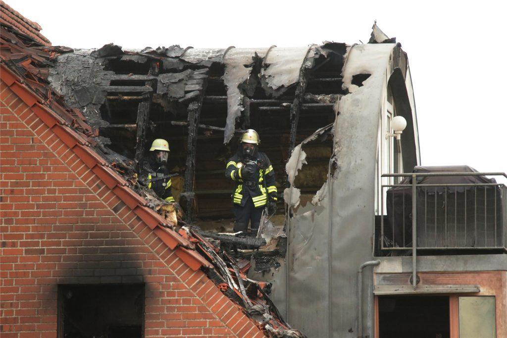Feuerwehrleute suchen in einem beschädigten Wohnhaus nach Spuren.