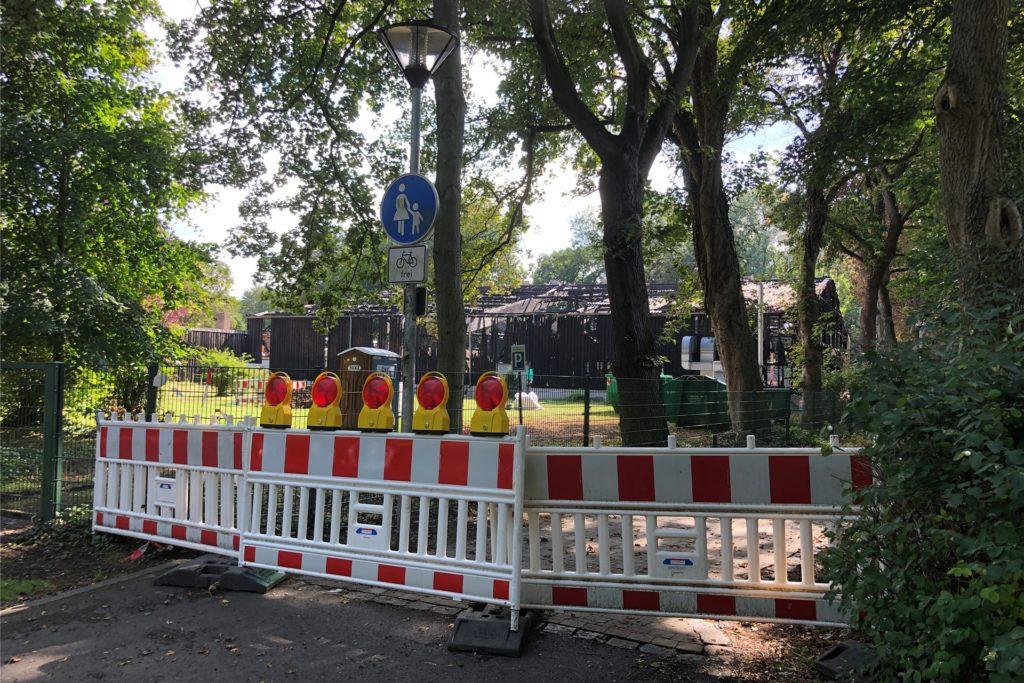 Der Fußweg führt direkt an der Brandruine der Tennishalle vorbei und ist deswegen abgesperrt. Doch die Gitter aus Plastik werden von vielen Spaziergängern beiseite geschoben. Die Stadt hat die Absperrungen nun verstärken lassen.