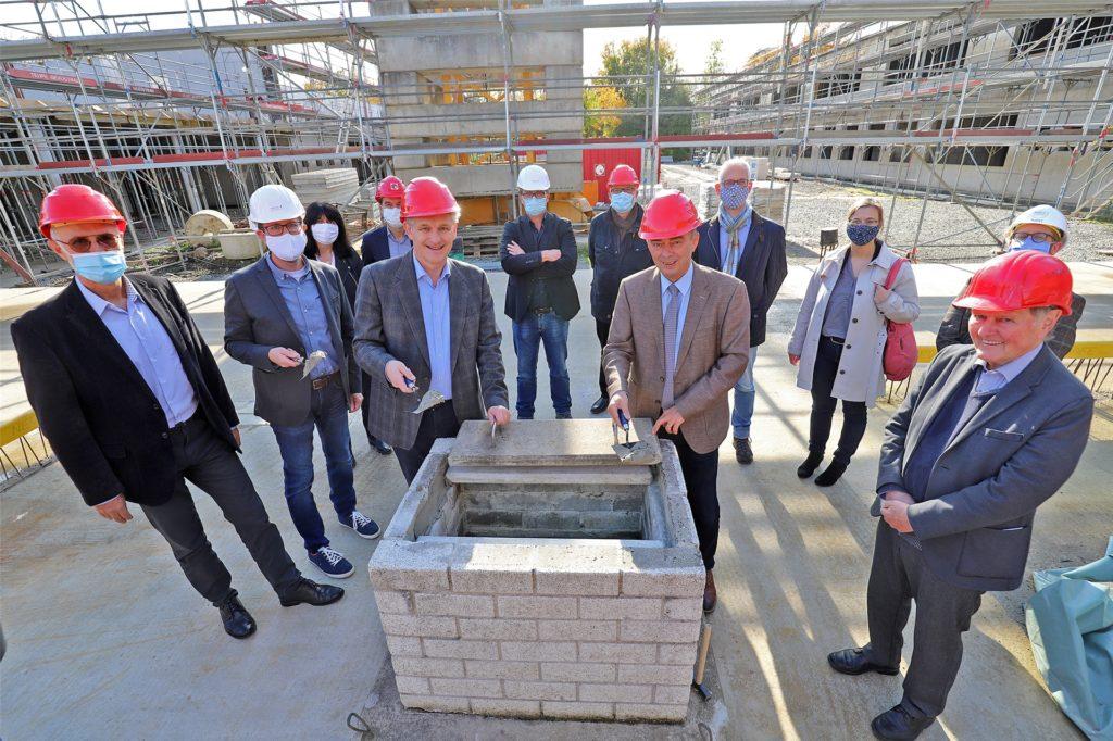 Die symbolische Grundsteinlegung markiert den Beginn der Bauarbeiten am Bildungscampus. Tatsächlich stehen die meisten Gebäude aber bereits im Rohbau.