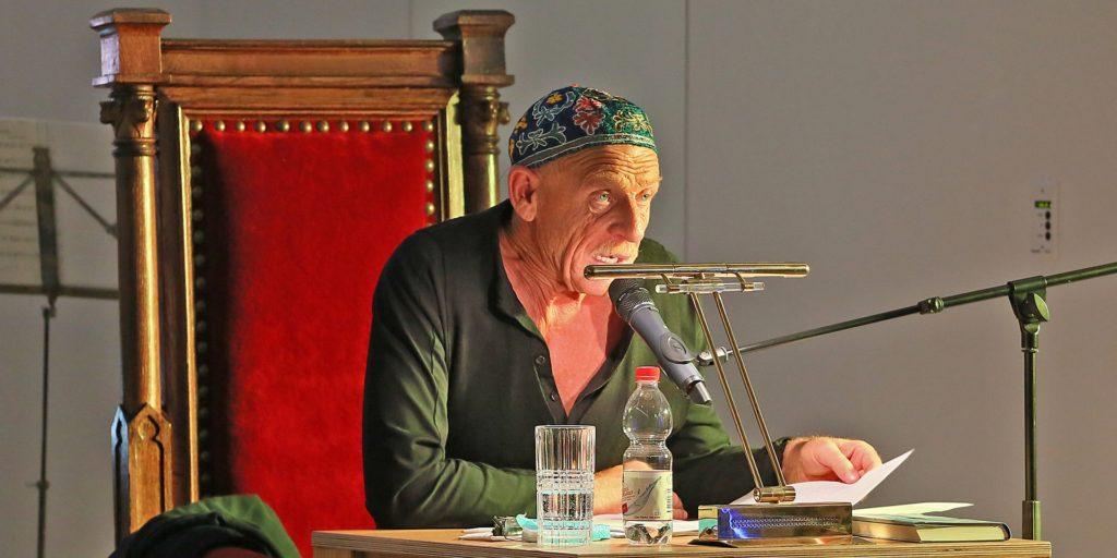 Joe Bausch las in der Synagoge. Auf dem Kopf trug er eine Kippa, die Alexandra Khariakova aus Jerusalem mitgebracht hat. Der Stuhl, auf dem er Platz nehmen durfte, war ein alter Richterstuhl, den die Gemeinde aus dem Amtsgericht besorgt hatte.