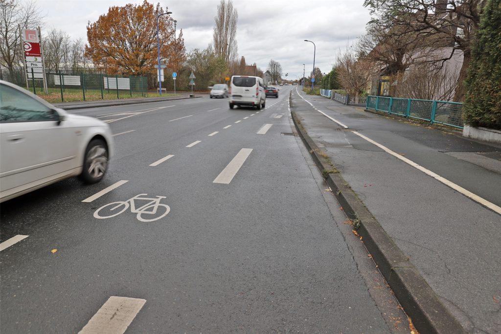 Dieses Bild zeigt einen Radweg – und zwar am rechten Rand auf dem Bürgersteig. Der vermeintliche Fahrradschutzstreifen schützt Radfahrer nicht, in der er ihnen eine Fahrspur bietet, sondern in dem er eine Abstandsbereich ausweist, den keine Kraftfahrzeuge befahren dürfen.