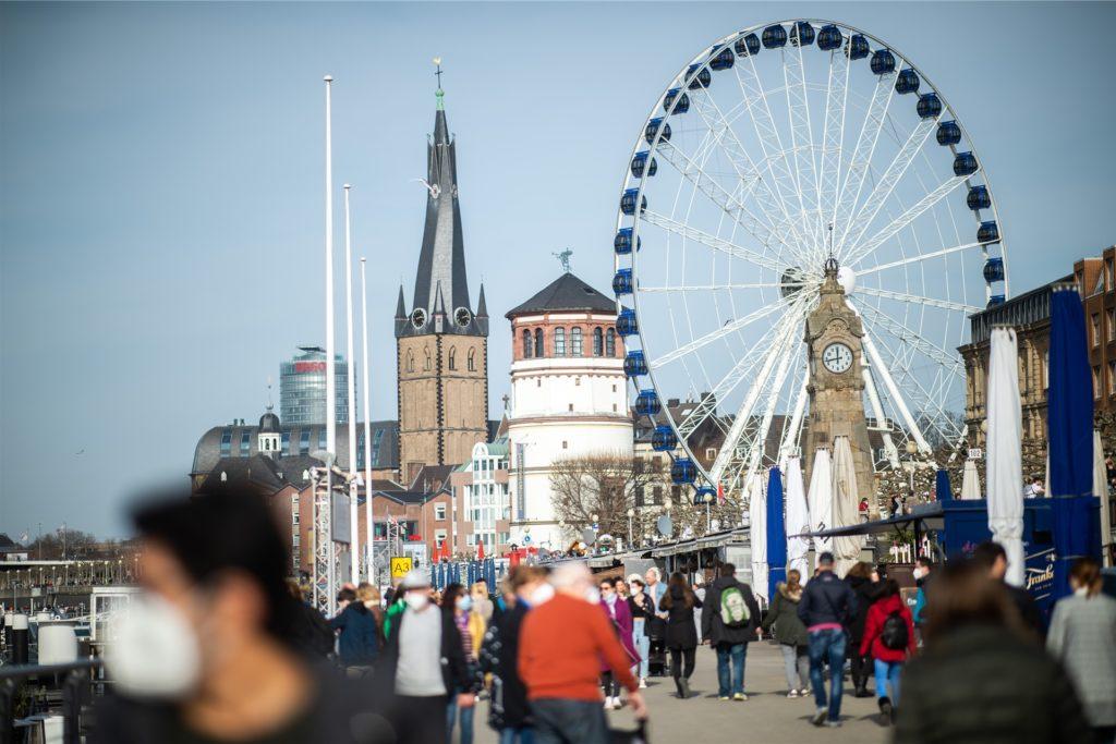 Menschen gehen bei Sonnenschein und frühlingshaften Temperaturen die Rheinuferpromenade in der Nähe des Burgplatzes entlang.