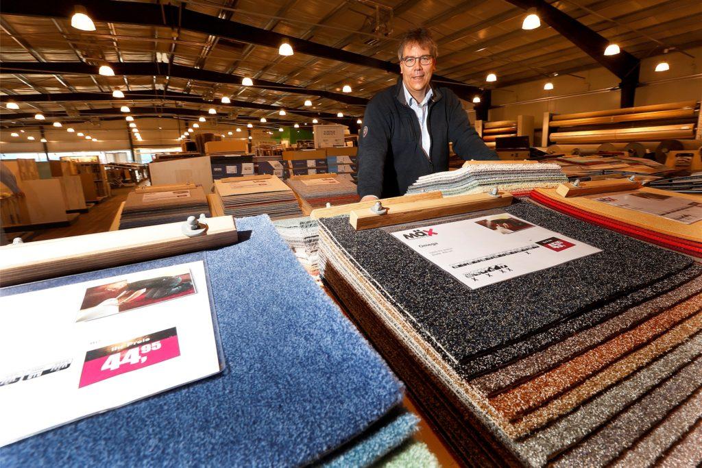"""Geschäftsführer Karsten Kemmer vor Teppich-Mustern in seinem Fachmarkt """"MäX"""" im Kamen-Karree. Er hofft darauf, dass sein Markt rasch wieder öffnen kann."""