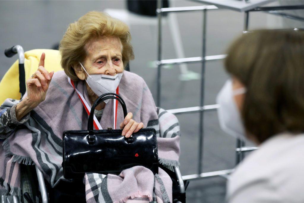 Elisabeth Steubesand (l, 105) spricht im Impfzentrum vor ihrer Impfung mit Henriette Reker, Oberbürgermeisterin von Köln.