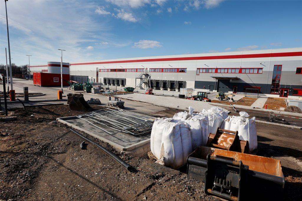 Neues Tedi-Zentrallager zwischen Zollpost und Henry-Everling-Straße in Kamen: Die Arbeiten an den Außenanlagen laufen teilweise noch, während innen bereits erste Ware eingelagert wird.