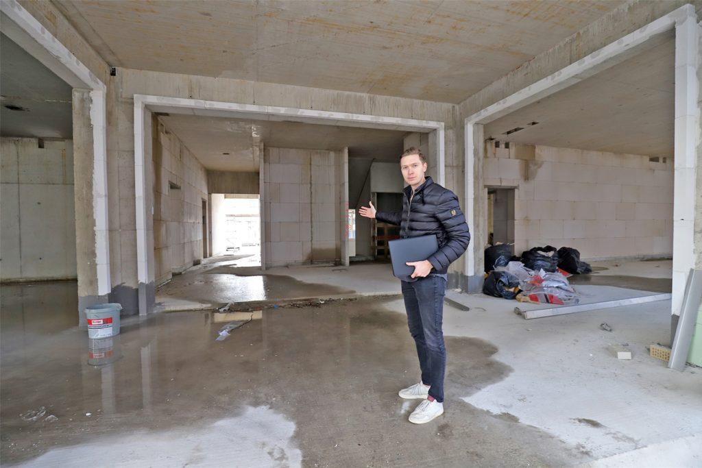 Willkommen in der Villa Möcking: Projektleiter Maximilian Kirchhoff im Eingangsbereich des neuen Hauses. Rechts und links sind die Eingänge zweier Ladenlokale, geradeaus geht es in den künftigen Hausflur mit Aufzug.