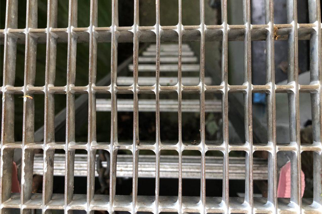 Der Lichtschacht zum Kriechkeller ist vergittert, kann aber offenbar von außen geöffnet werden. An einer Stelle ist zu erkennen, dass das Metall verbogen wurde.