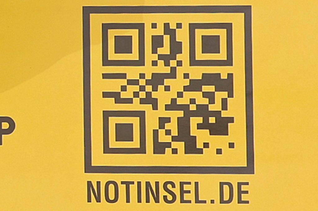Jörg Theis, Vorsitzender des Awo-Stadtverbands, zeigt ein leuchtend gelbes Schild mit dem Hinweis auf eine Notinsel. Die Awo betreut auf Kamener Stadtgebiet 72 Anlaufstationen für Kinder.