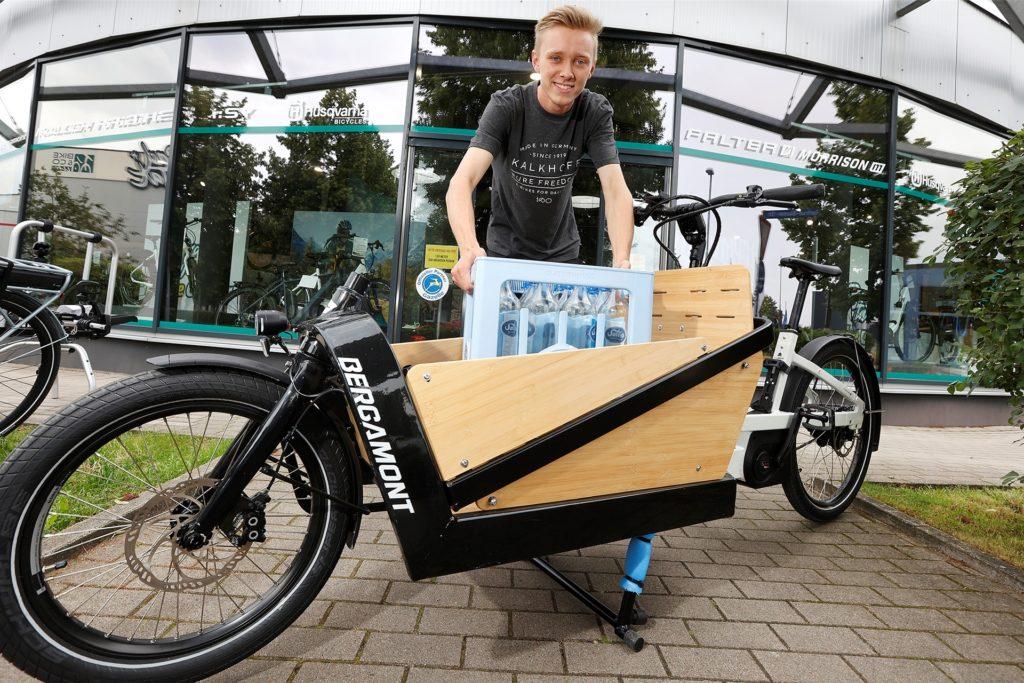 Noah Hübner packt eine Kiste Wasser in die Transportbox. Der Stauraum reicht auch für einen Großeinkauf.