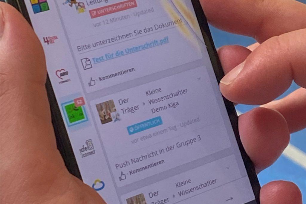Auf dem Handy stehen alle Infos aus der Kita in einer App parat.