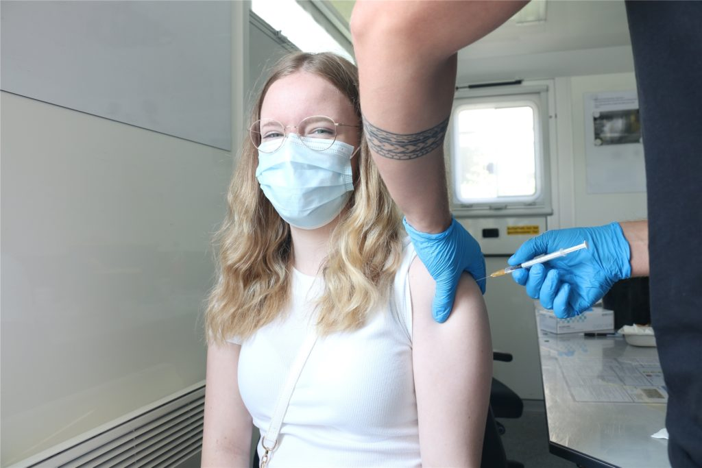 Lukas Chronz verimpft eine Dosis Biontech bei der 16-jährigen Sarah Tönjann.
