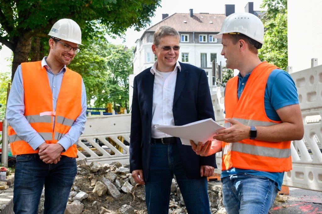 Der Leiter des Projekts Fernwärme, Bastian Stegemann, von DEW21, Baudezernent Arnulf Rybicki und Ingmar Luther, Leiter Stadtarchäologie Dortmund, beim Pressetermin an der Stadtmauer.