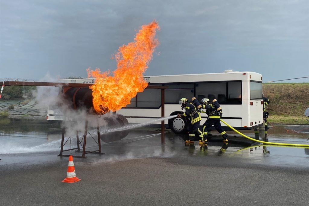 Zwei Feuerwehrleute löschen Flammen aus einem ausgebauten Triebwerk. Daran wird ein echter Brand simuliert.