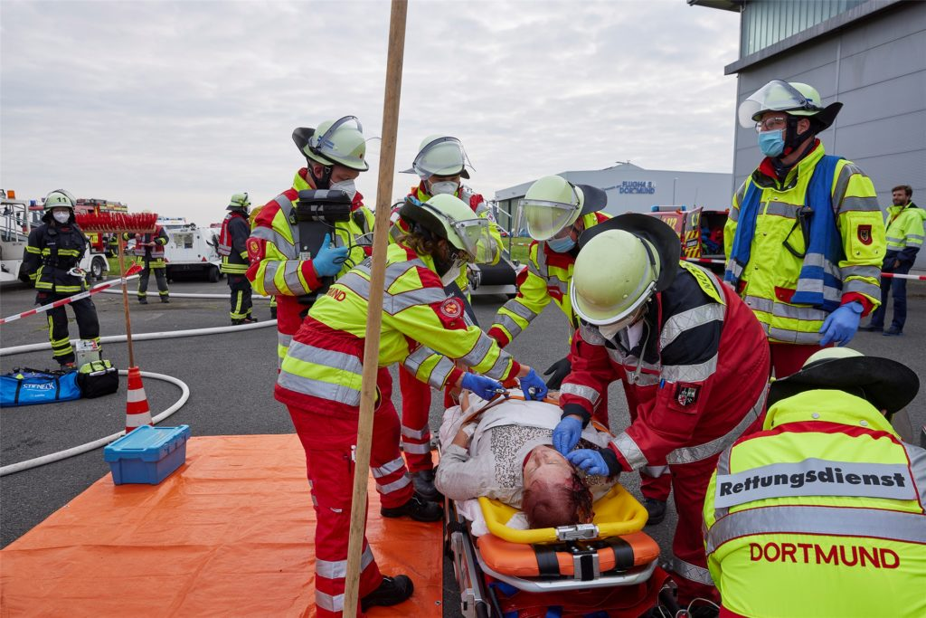 Unfalldarstellerin mit Platzwunde aus Kunstblut wird von Rettungskräften versorgt.