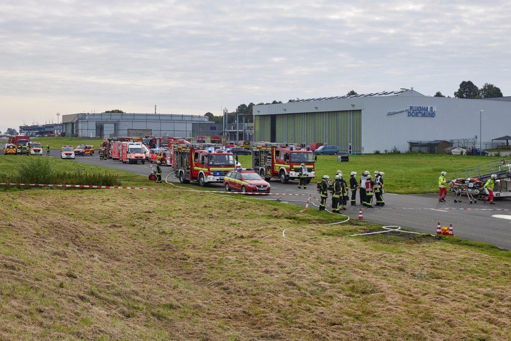 Mehrere Einsatzwagen und ein Gewimmel aus Einsatzkräften: Lagebild des Einsatzes am Flughafen
