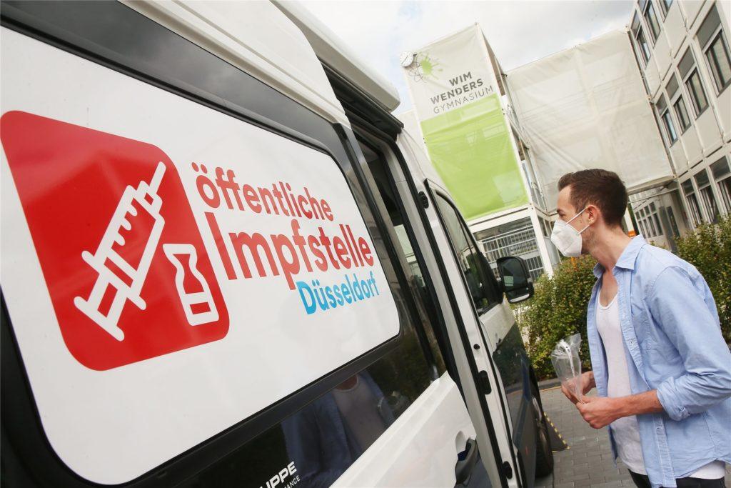 Vor einem Wahllokal in einer Schule lässt sich ein junger Mann an einer mobilen Impfstation über eine Covid-19-Impfung beraten.